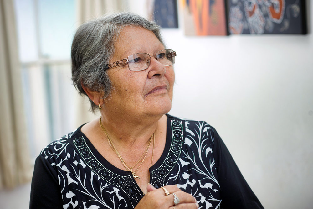 Indigenous community leader and Elder, photographed in a pensive pose in fron of a number of her art works. Photo by Ian Mckenzie, Mildura Photographer.