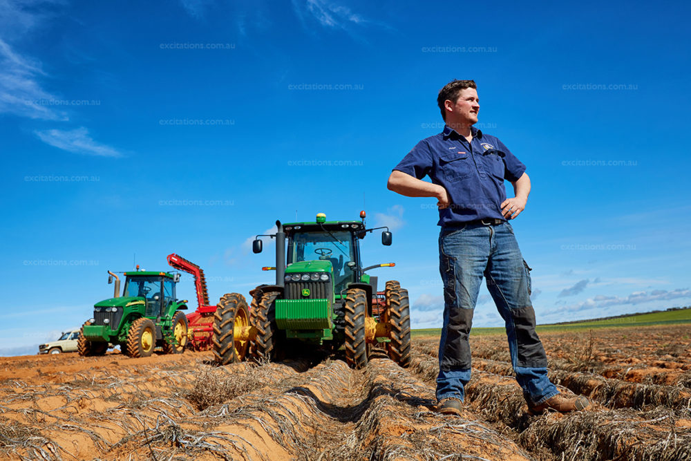 Farmer stands in fron of huge John Deere tractors in potato field. Photo by Mildura photographer, Excitations.