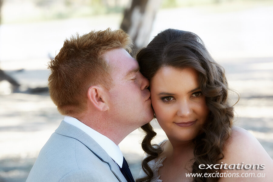 Closeup of groom kissing bride doing wedding photography session. Amy and Tony's wedding photography by Excitations, photographers Mildura.