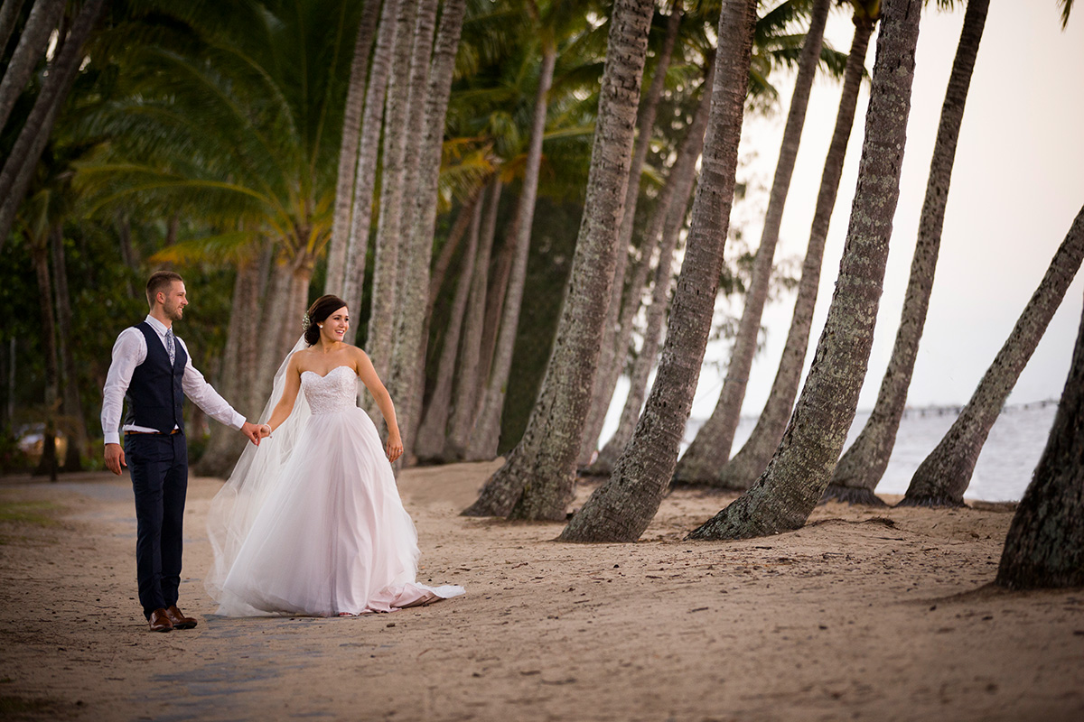 Bride and groom walk hand in hand along beachfront at Palm Cove, Northern Queensland. Wedding photography by Excitations, photographers Mildura, Sunraysia, Australia.