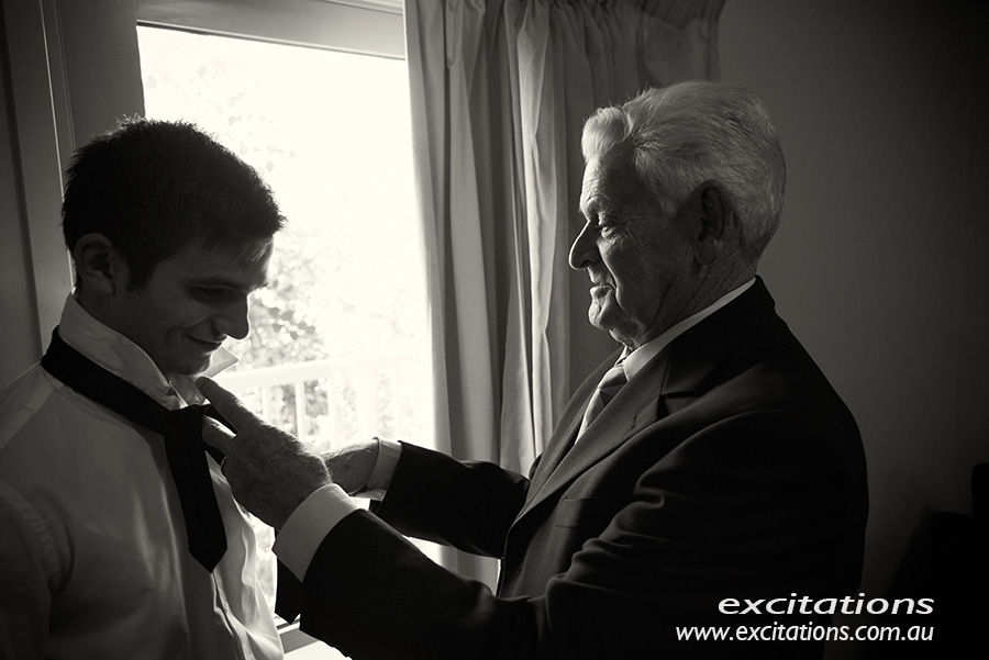Black and white wedding photo of grandfather fixing grooms tie. Photography, Excitations Mildura wedding photographers.