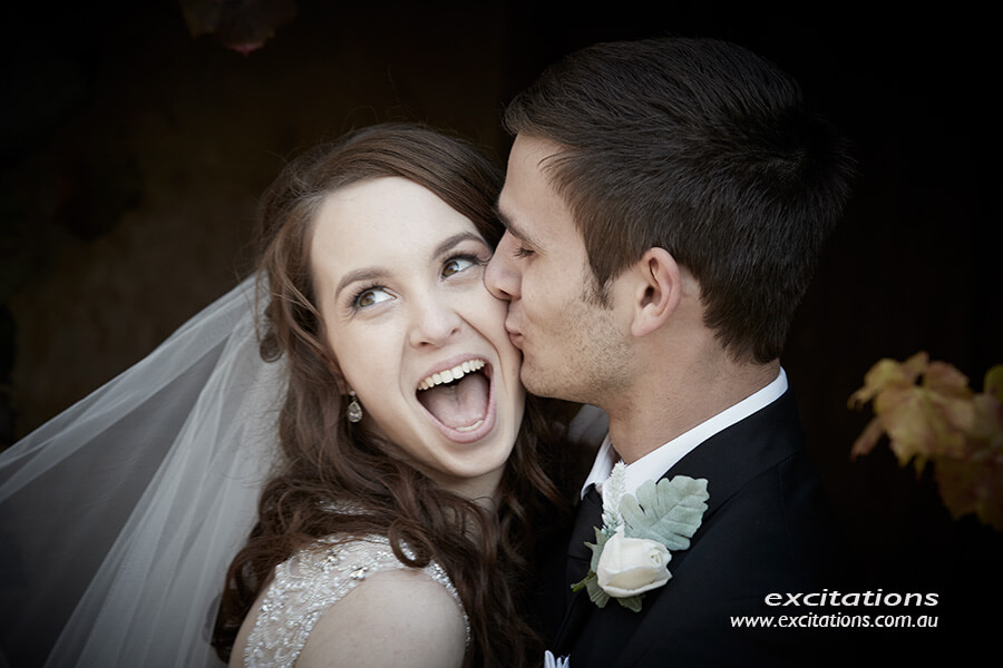 Q Estate Wedding photography location. Very happy bride being kissed on cheek by groom.