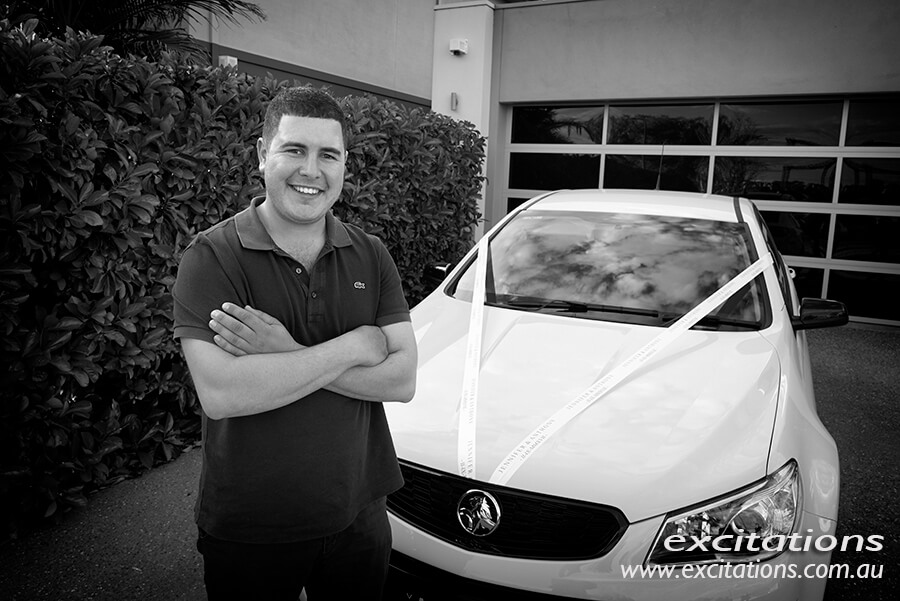 Groom dressed casually, standing arms folded in front off his car which was the bridal car for the wedding day. Wedding photographer in Mildura.