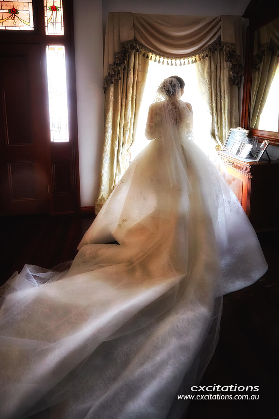 Warm romantic full length photograph of bride from behind. Featuring beautiful natural light, a stunning wedding dress. Sunraysia wedding photography by Excitations.