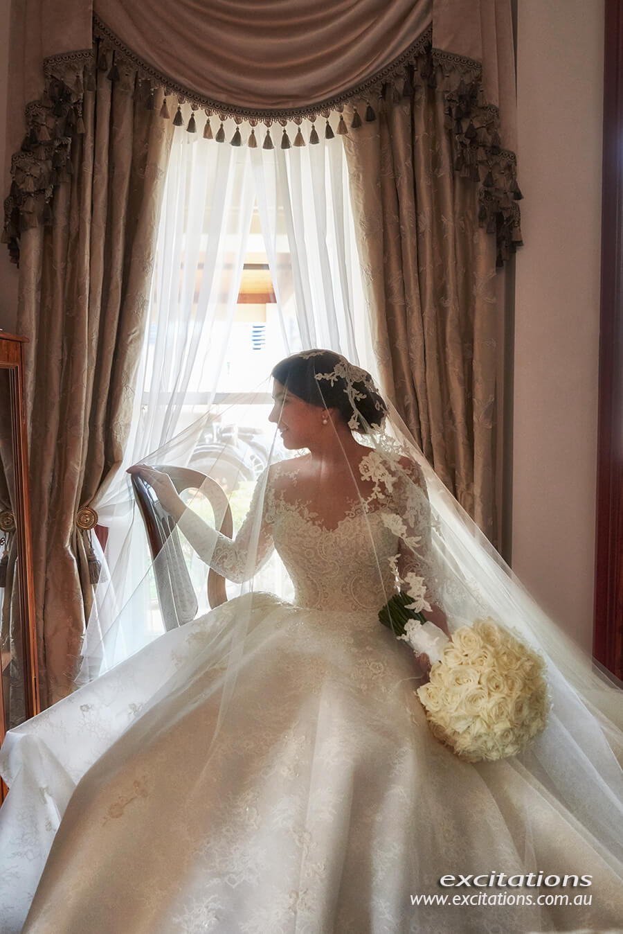 Bride seated in front of a window in a soft, romantic wedding portrait. Mildura wedding photography by Excitations.