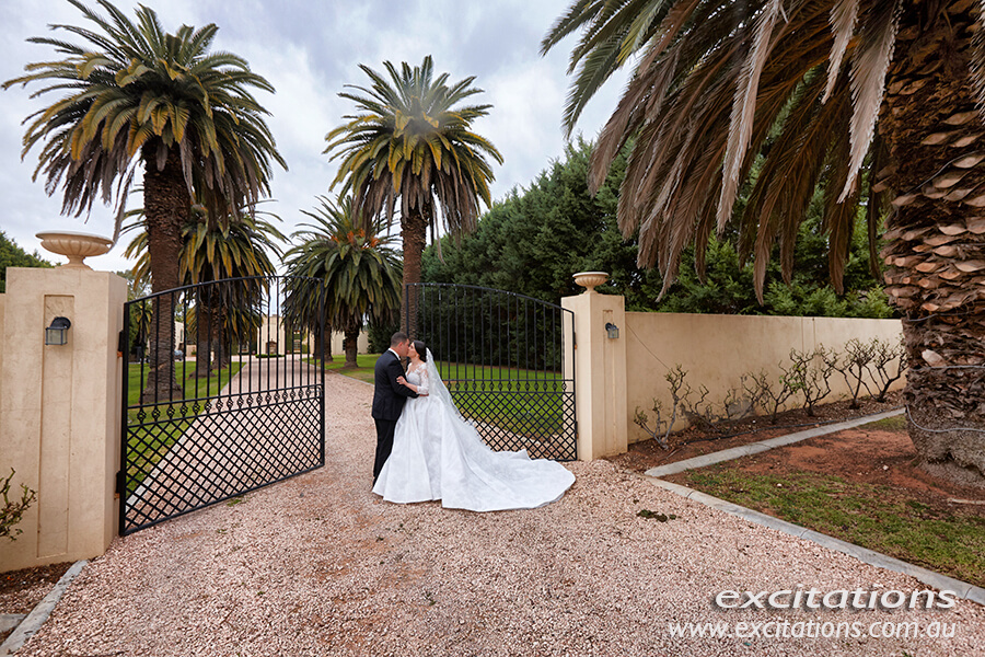 Wide angle wedding photograph of bride and groom in front of fenced garden with a large gate. Sunraysia wedding photography by Excitations, Mildura.
