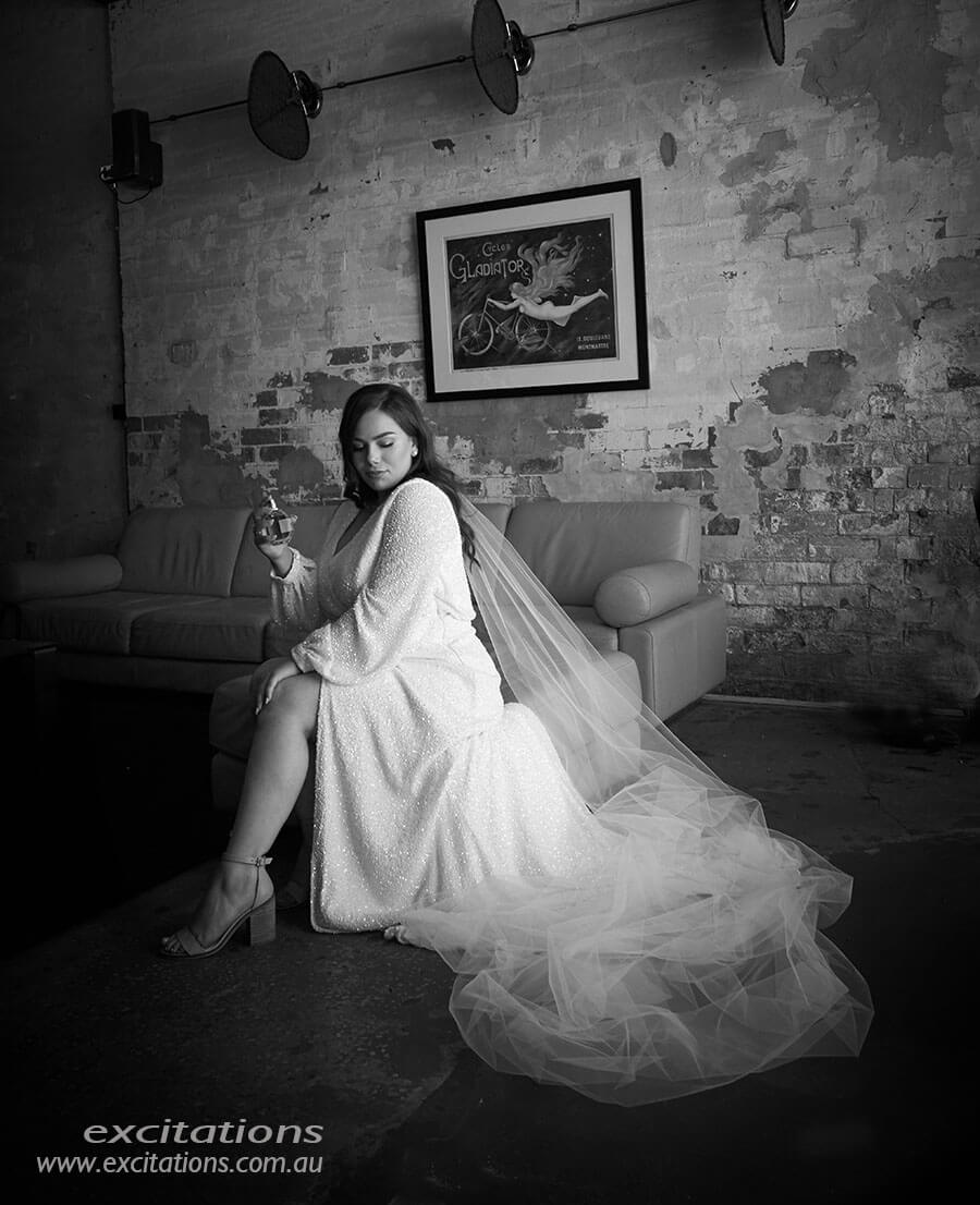 Black and white photo of bride. Full length indoors seated. Married in Mildura, photography by Excitations