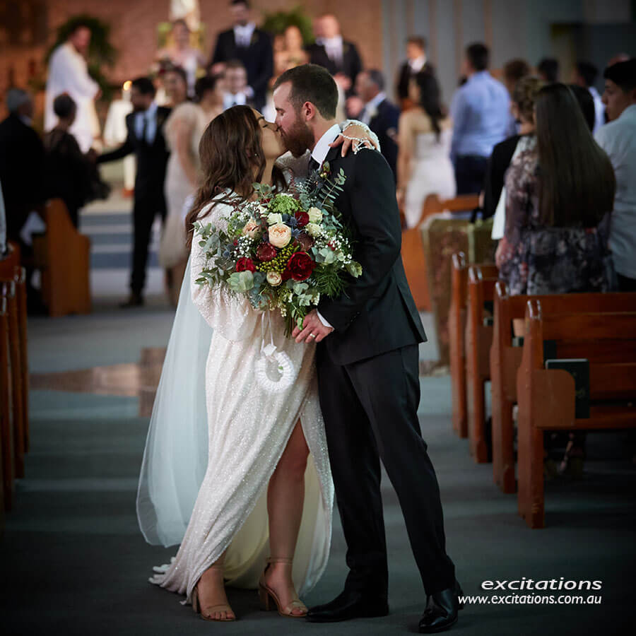 Bride and groom stop to kiss as they walk down the aisle in Sacred Heart Church, Mildura.