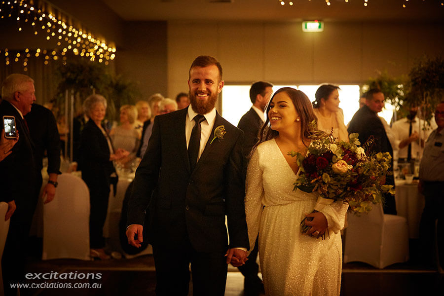 Golden light on bride and groom as they walk into club Da Vinci, Mildura.