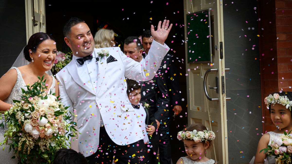 Happy bride and groom exiting church with confetti in the air, Excitations Mildura Photographers