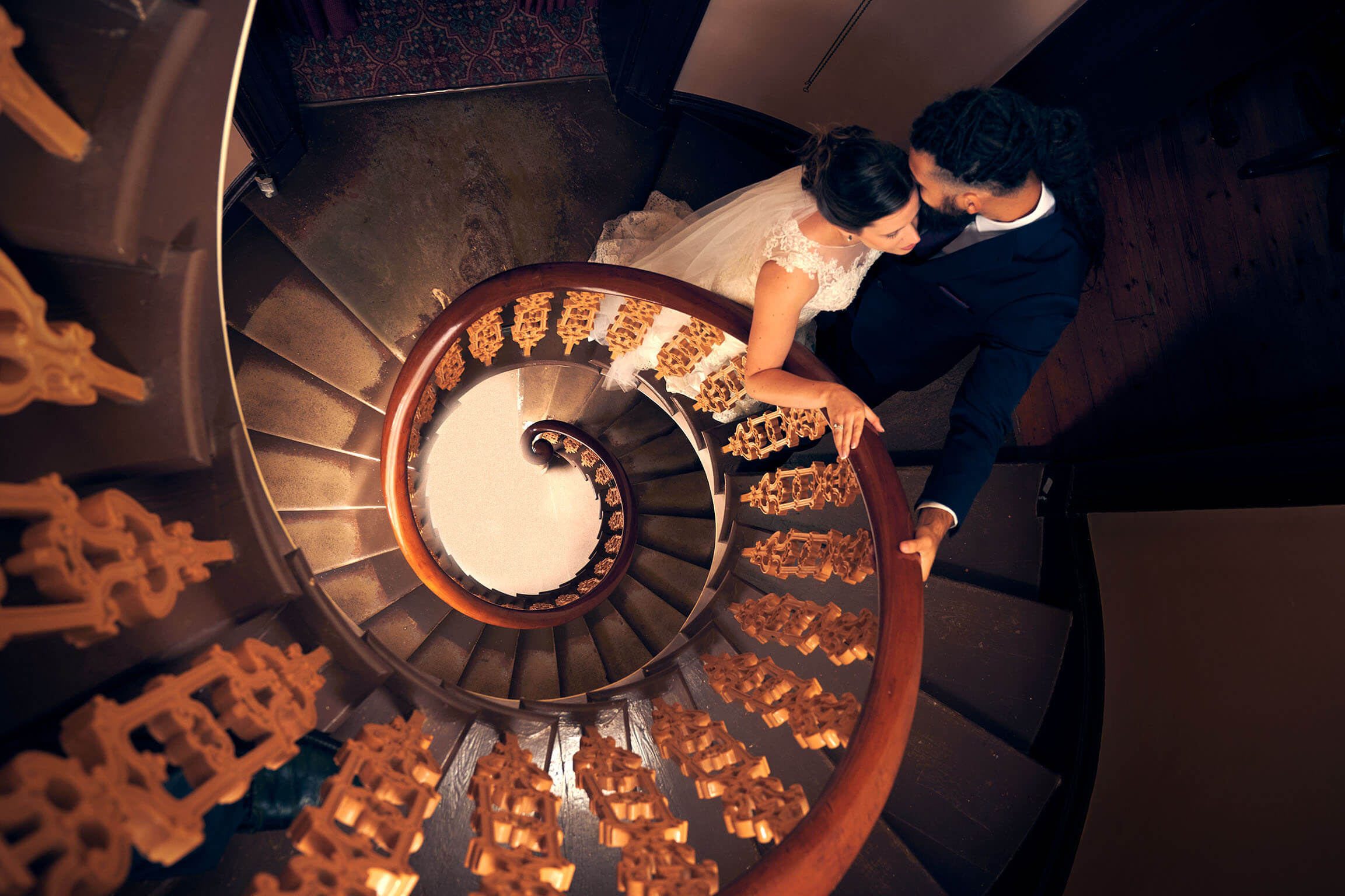 Looking down on bride and groom on a spiral staircase. Photo by Excitations photographers Mildura